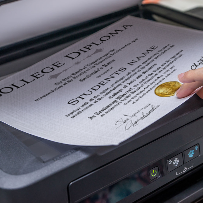 college diploma with shiny gold state seal being scanned and photocopied on copy machine